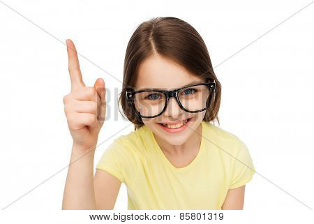 education, school and vision concept - smiling little student girl in eyeglasses pointing finger up