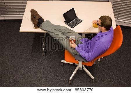 man sitting at with legs on the desk with hamburger and mug, heaving break for meal in office
