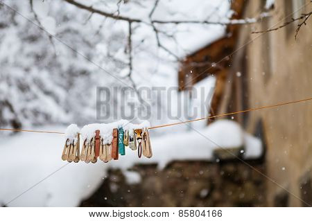 Clothespins on a rope under snow