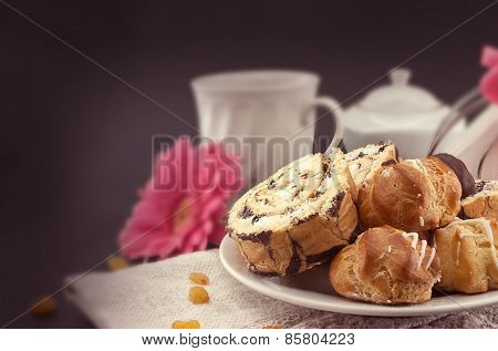 Cake Roll And Eclair On Plate With Coffee On Dark Background, Selective Focus.