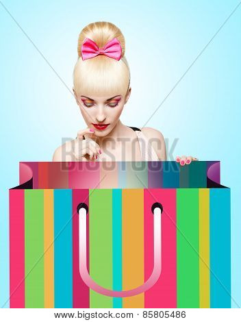 Glamorous girl looking into huge shopping bag on blue