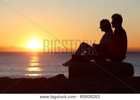 Couple Silhouette Sitting Watching Sun At Sunset