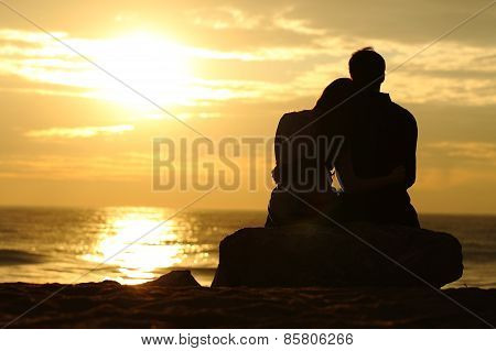 Couple Silhouette Watching Sunset On The Beach