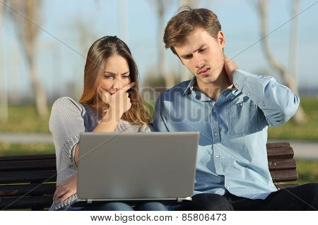 Worried Students Or Entrepreneurs Watching A Laptop Outdoors