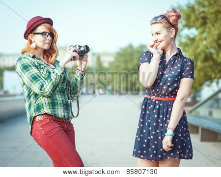 Two Beautiful Hipster Girls Taking Pictures On Film Camera Outdoor