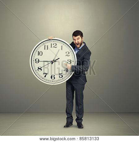 emotional businessman holding big white clock, pointing, screaming and looking at camera against dark background