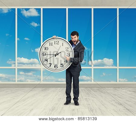 screaming angry businessman with big clock in room with windows