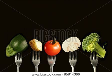 Variation of fresh vegetables on a black background, zucchini, potato, tomato, mushroom and broccoli