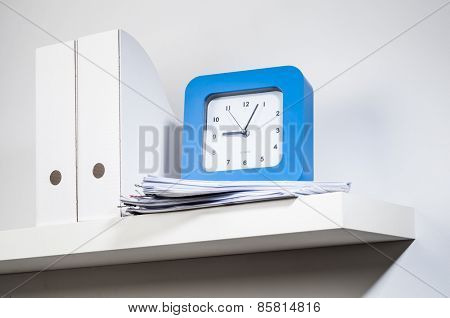 Big clock, paper file and documents placed on the white shelf.