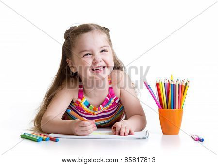 Happy little girl drawing with felt-tip pen in preschool