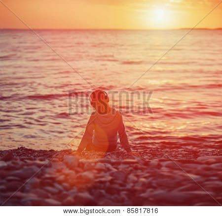 Girl In Headphones Sitting On Beach At Sunset
