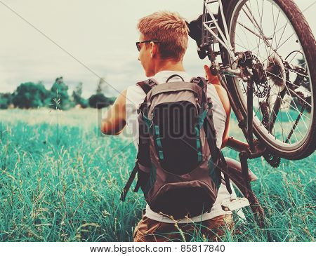 Cyclist Carries Bicycle In Green Meadow