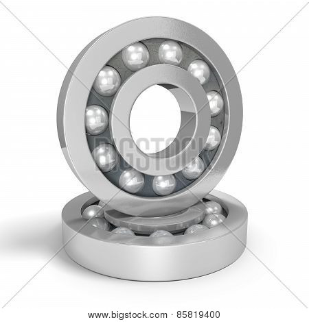 Two shiny steel ball bearings on a white background, one balanced on the other