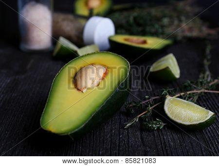 Sliced avocado with lime and herb on wooden background