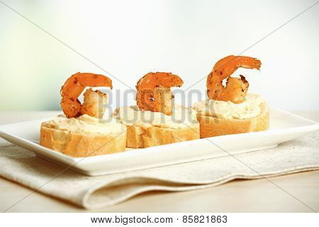 Appetizer canape with shrimp on table on light background