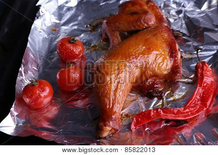 Smoked chicken leg with cherry tomatoes on foil close up