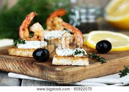Appetizer canape with shrimp and lemon on cutting board on table close up