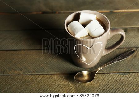 Cup of cocoa with marshmallows on rustic wooden planks background
