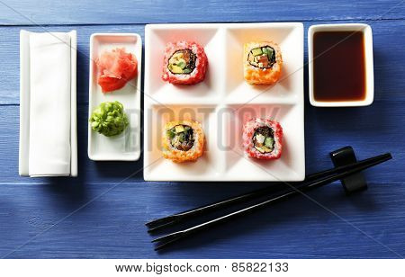 Sushi rolls on plate, soy sauce and chopsticks on color wooden background