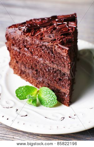 Delicious chocolate cake in white plate with mint on wooden table background, closeup