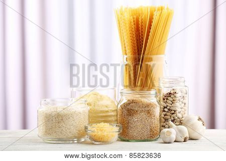 Different products on wooden table on curtain background