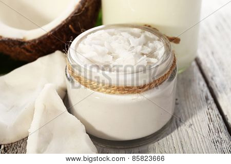 Fresh coconut oil in glassware on color wooden table background