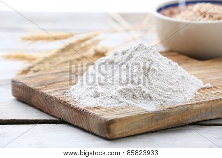 Heap of flour on cutting board with ears and grains in bowl on wooden table
