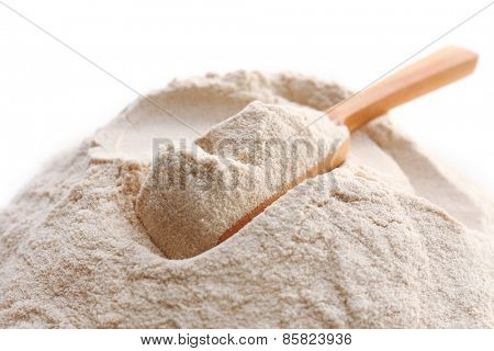 Heap of flour with wooden spoon isolated on white