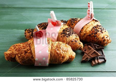 Fresh and tasty croissants with chocolate on color wooden background