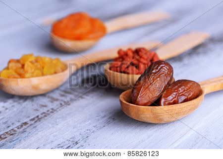 Dried fruits in spoons on color wooden table background