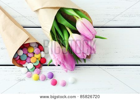 Beautiful pink tulips in paper with sweets on wooden background