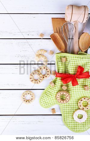 Set of kitchen utensils with cookies in mitten on wooden background