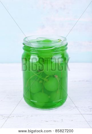 Homemade jar of green maraschino cherry on wooden table and color wall background