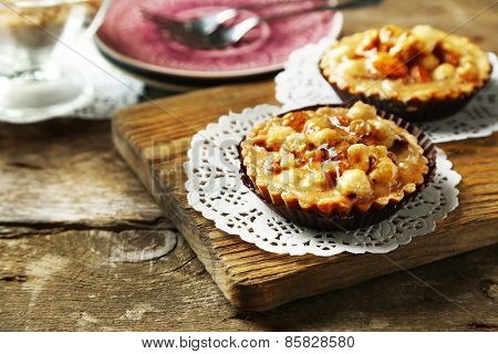 Mini cakes with nuts on wooden background