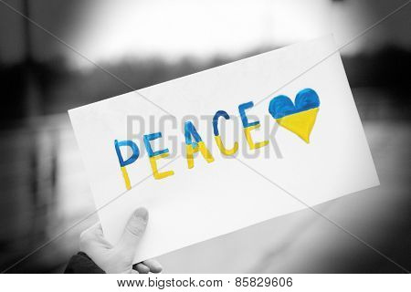 Hand holding paper with Peace of Ukraine