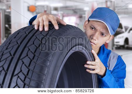 Male Technician Controls A Tire