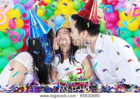 Parents Kissing Their Child In Birthday Party