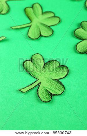 Shamrock leaves on green background