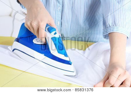 Woman ironing shirt on ironing board in room