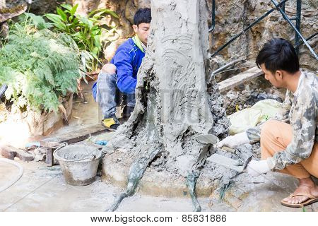 Workers Are Grout Cement On The Fake Tree Trunk