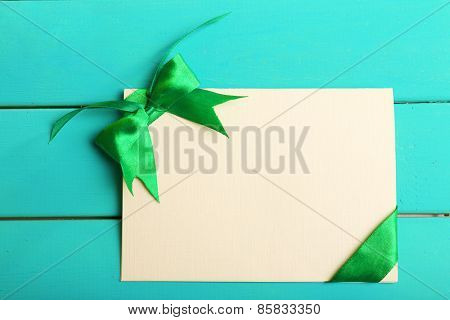 Card decorated with green bow on wooden background