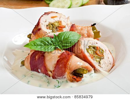 Delicious chicken rolls stuffed with green beans and carrots wrapped in strips of bacon with yoghurt