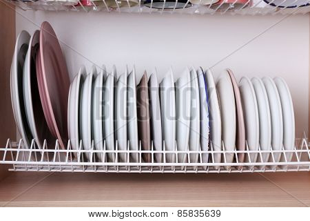 Clean plates drying on metal dish rack on shelf