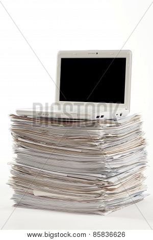 Laptop over pile of documents