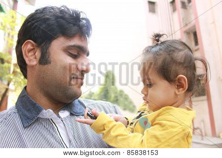 Young Indian man holding his daughter and looking at her with love