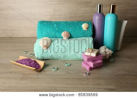 Spa composition with towels and sea salt on wooden background