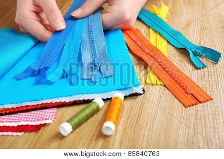 Colorful fabric samples and zipper in female hands on wooden table background