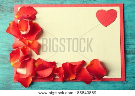 Beautiful hand made post card with rose petals on color wooden background