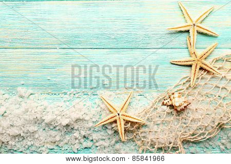 Sea stars on sea salt on wooden background