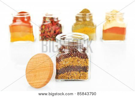 Different kinds of spices in glass bottles isolated on white